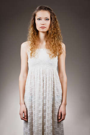 seriously: beautiful curly haired woman standing strait portrait Stock Photo