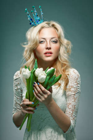 blonde girl wearing princess crown holding white tulips photo