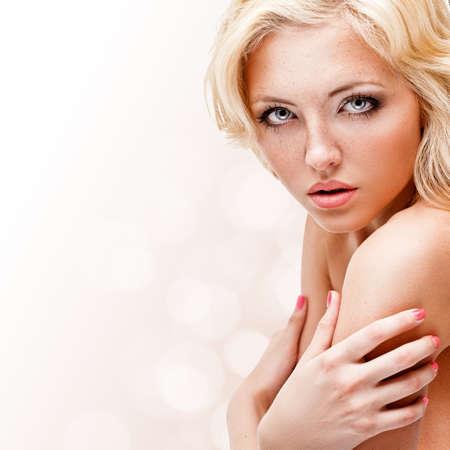 salud sexual: mujer rubia con pecas en la cara, retrato del primer puro sobre fondo blanco