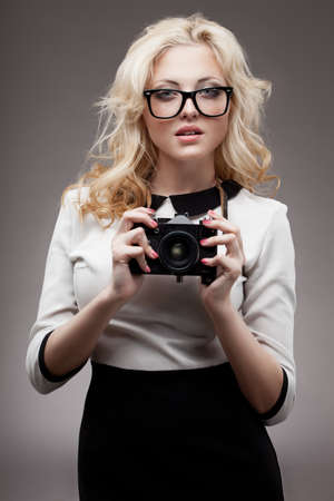 beautiful blonde girl holding retro camera wearing eyeglasses photo