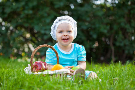 closeup portrait of baby girl sitting on the grass near basket with fruits photo