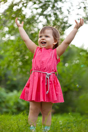 people clapping: little girl stands on a meadow with raised hands