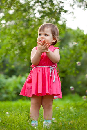 cute little girl in pink dress stading on meadow and clapping hands photo