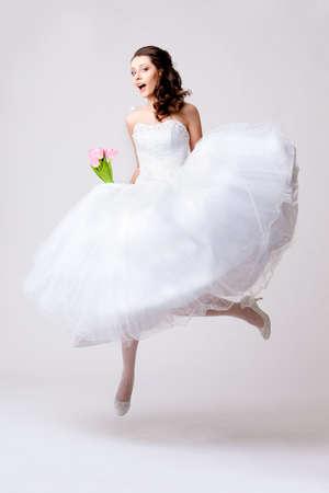 salto largo: funny hermosa novia saltando en estudio sobre fondo blanco Foto de archivo