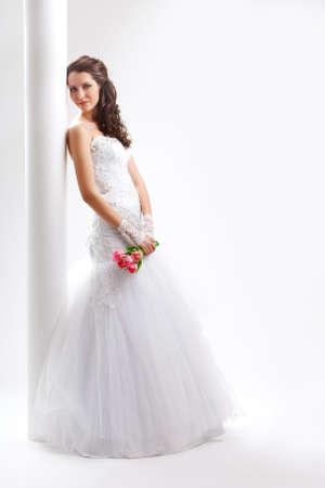 beautiful bride standing back to the  white column, studio shot
