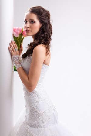 mooie bruid die zich dichtbij witte kolom, studio opname