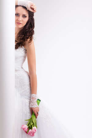 beautiful bride standing behind white column, studio shot photo