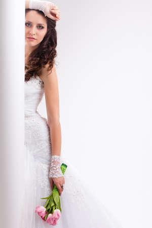 beautiful bride standing behind white column, studio shot photo