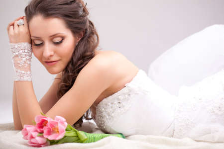 beautiful bride: studio photograph of a bride posing on the floor and looking to the bouquet