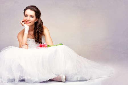 smiling beautiful brunette  bride sitting on the floor, vintage style photo