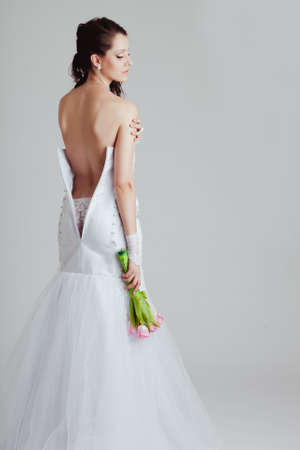 a  bride with a bare back dress over white background photo