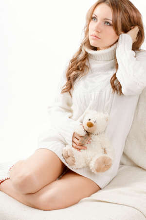 beautiful sexy woman wearing sweater sitting on the sofa and holding soft toy photo