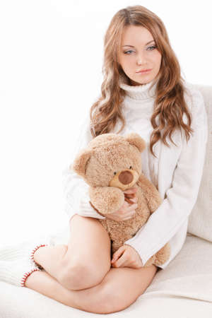 sweater girl: beautiful sexy woman wearing sweater sitting on the sofa and holding soft toy