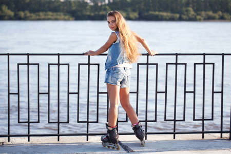 rollerskating: girl on roller skates is worth holding on to the railing