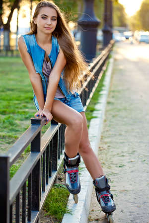 roller skate girl wearing jeans sitting on iron fence over sunset photo