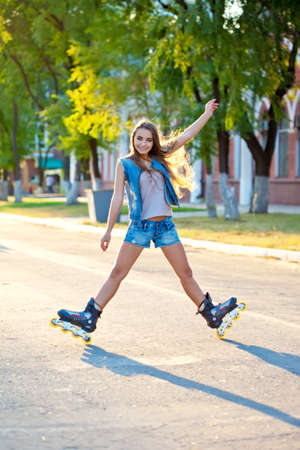 beautiful woman skating outdoors  during sunset photo