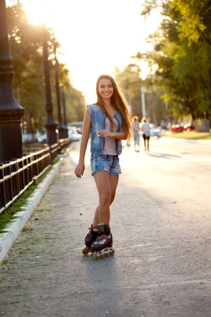 rollerblading: happy smiling woman skating outdoors  during sunset