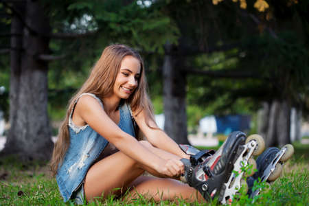 smiling girl sitting on the grass in park and puts on skates photo