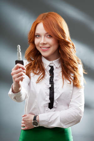 red haired: happy red haired woman holding big key Stock Photo