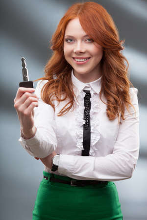 red haired woman: happy red haired woman holding big key Stock Photo