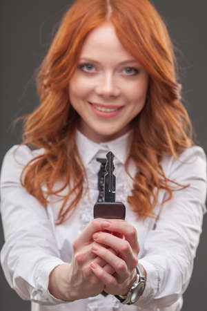 happy red haired woman holding big key photo