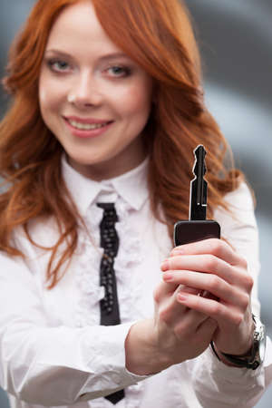 red haired woman: happy red haired woman giving big key