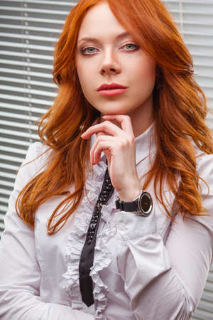 venetian blind: red-haired businesswoman standing over blinds, close up portrait