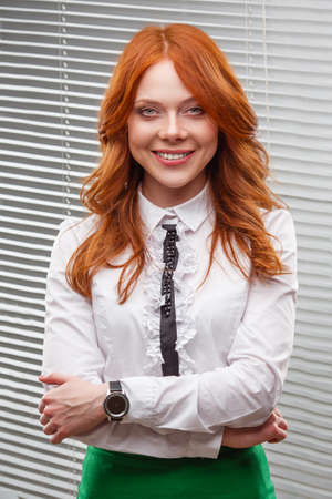red-haired businesswoman standing over blinds photo