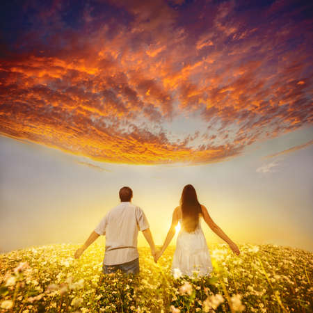 young couple holding hands and walks away into the sunset