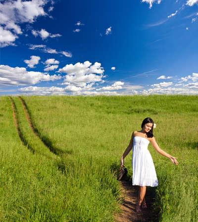 woman walking along the road through green filed