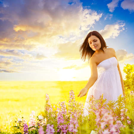 beautiful brunette woman walking in a field at sunset and touching flowers Banque d'images