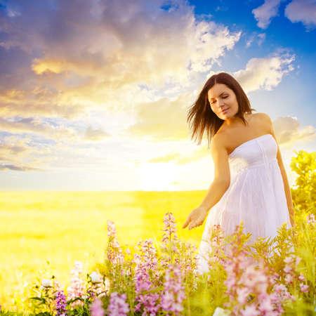 beautiful brunette woman walking in a field at sunset and touching flowers Standard-Bild