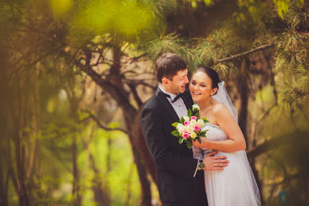 happy bride and groom in conifer trees park