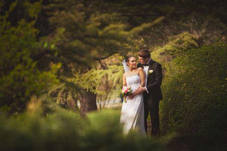 happy bridal couple walking in park