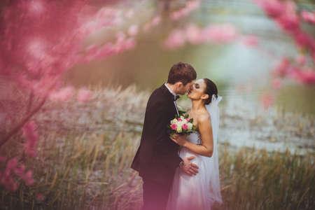 happy bridal couple kissing in park Standard-Bild