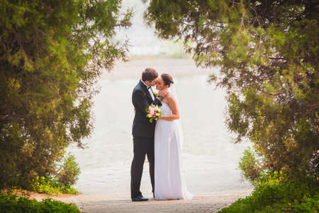 bridal veil: bride and groom outdoors park under trees arc