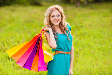 happy blonde woman at park posing with shopping bags