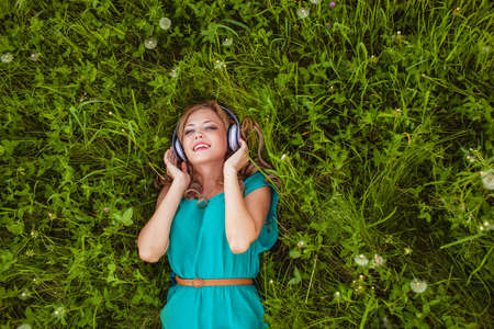 woman laying on green grass with headphones photo