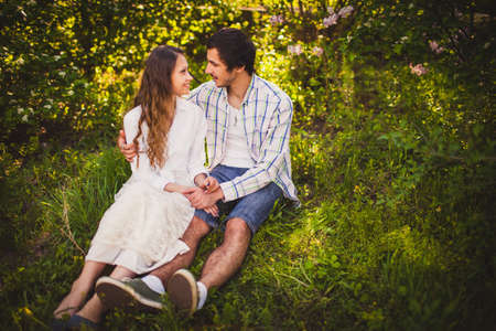 jovenes enamorados: pareja de adultos jóvenes en el amor sentados y abrazos en el parque de verano