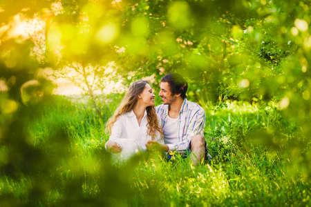 lächelnden Erwachsenen Paar in der Liebe sitzen und umarmt auf Sommerpark