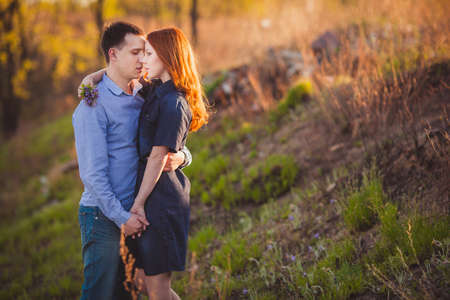 lovely couple: young couple kissing standing outdoos among bushes