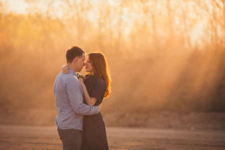 redhaired: young couple embracing standing on the road in the dust