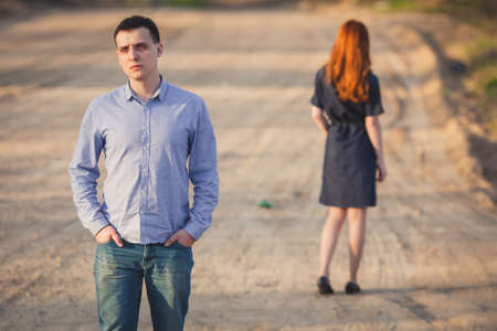 family problems: sad man and red woman stand on the dirt road Stock Photo