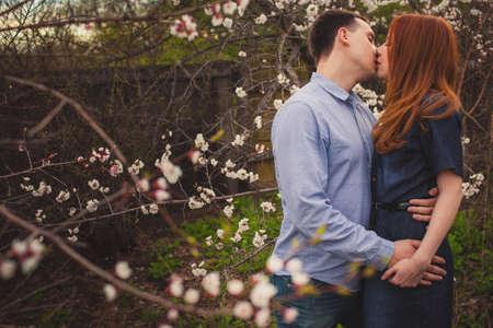 schöne Paar küssen unter den blühenden Bäumen