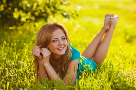 freckles: happy blonde woman lying on grass at park