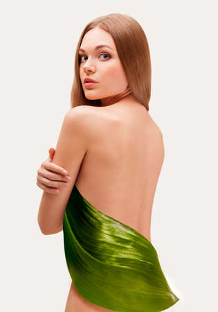 beautiful woman covering with big green leaf photo