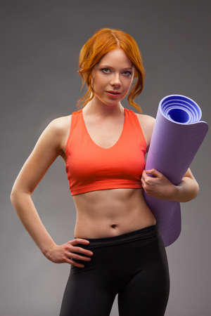 red -haired woman holding fitness mat photo