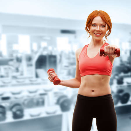 red-haired happy woman excersising with red dumbbells over gym interior photo