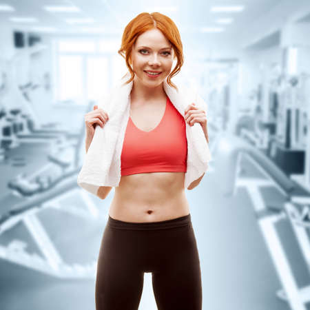 red-haired happy woman standing with towel over gym interior photo