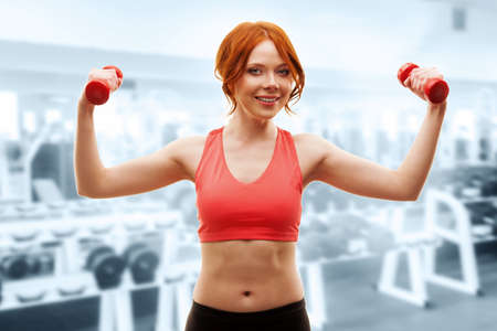 red -haired happy woman excersising with red dumbbells over gym interior photo